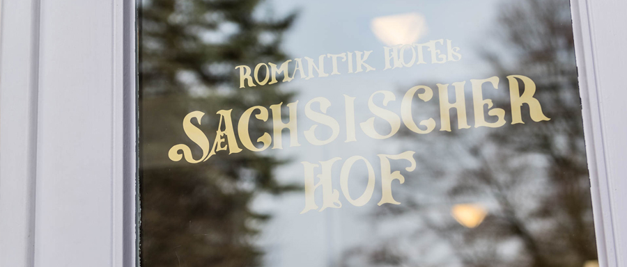 Logo Romantik Hotel Sächsischer Hof on a window pane of the hotel